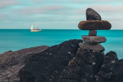 Composed rocks on shore with sailing ship stock photo