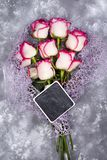 Composed of the roses and chalkboard. Wonderful flatlay composed of the roses and chalk board on gray stone background, flat lay royalty free stock photography