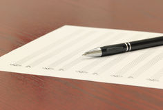 Composer. Blank staff paper and mechanical pencil on a wooden desk Stock Image