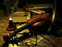 Composer's desk. Vintage composer's desk enlightened by a candle, with violin, glasses, several musical scores and other objects Royalty Free Stock Photography