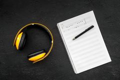 Composer and song writer desktop with headphones and notes on black background top view mock up. Composer and song writer desktop with headphones and notes on Stock Photos