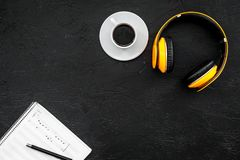 Composer and song writer desktop with headphones and notes on black background top view mock up. Composer and song writer desktop with headphones and notes on stock photo