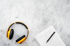 Composer and song writer desktop with headphones and notes on stone background top view mock up. Composer and song writer desktop with headphones and notes on stock images