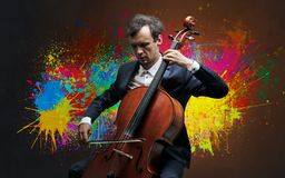 Composer with splotch and his cello. Young classical musician with colorful splotch wallpaper
