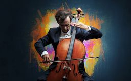 Composer with splotch and his cello. Young classical musician with colorful splotch wallpaper royalty free stock photography