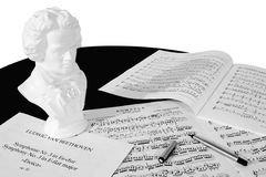 Composer at Work (Black and White). A bust of Beethoven, three scores and a fountain pen atop a black piano, isolated against a white background. Black and white Stock Image
