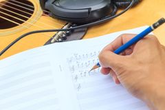 Composer write note of song and use acoustic guitar. For play royalty free stock image