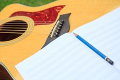 Composer write note of song and use acoustic guitar. For play in the park royalty free stock photo