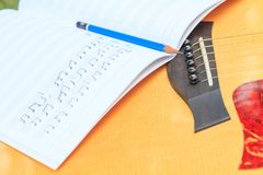 Composer write note of song and use acoustic guitar. For play stock image