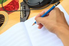 Composer write note of song. And use acoustic guitar for play royalty free stock images