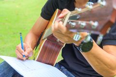 Composer write note of song and use acoustic guitar. For play royalty free stock photo