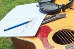 Composer write note of song and use acoustic guitar. For play royalty free stock photos