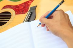 Composer write note of song and use acoustic guitar. For play in the park royalty free stock photos