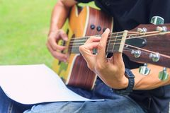 Composer write note of song and use acoustic guitar. For play in the park stock photography