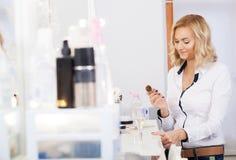 Composez l'artiste appliquant la poudre de visage à un client dans un magasin de beauté photographie stock