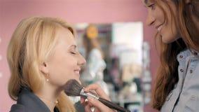Composez l'artiste faisant le professionnel de la jeune femme, brosse dans des mains de styliste Photo stock