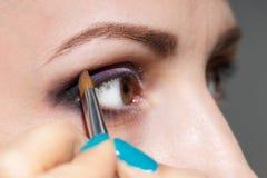Composez la femme appliquant la poudre de fard à paupières avec la brosse Photographie stock