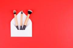 Composez les brosses avec l'enveloppe ouverte de blanc sur le fond rouge Photo stock