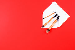 Composez les brosses avec l'enveloppe ouverte de blanc sur le fond rouge Photo libre de droits