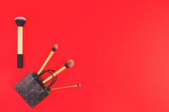 Composez les brosses avec le panier de livre blanc sur le fond rouge Photographie stock libre de droits