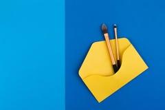 Composez les brosses dans l'enveloppe ouverte de jaune sur le fond bleu Photos libres de droits