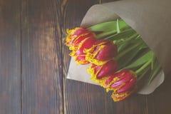 Composição à moda do ramalhete do vintage com as tulipas da cor do bi na tabela de madeira do marrom escuro Flores bicolores envo Fotografia de Stock