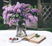 A composição bonita com livro velho e o ramalhete do lilás no vaso no vintage branco atam a toalha de mesa, fundo cinzento da par Foto de Stock