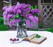 A composição bonita com livro velho e o ramalhete do lilás no vaso no vintage branco atam a toalha de mesa, fundo cinzento da par Imagens de Stock