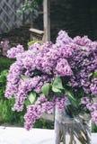 Composição bonita com o ramalhete do lilás no vaso na toalha de mesa branca do laço do vintage, fundo cinzento da parede de pedra Imagem de Stock