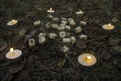 Composição bonita do Dia das Bruxas com runas, crânio, tarô e velas na grama no ritual escuro da floresta do outono Fotografia de Stock