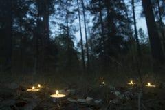 Composição bonita do Dia das Bruxas com runas e velas na grama no ritual escuro da floresta do outono Imagem de Stock