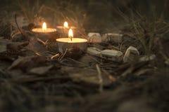 Composição bonita do Dia das Bruxas com runas e velas na grama no ritual escuro da floresta do outono Foto de Stock