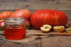 Composição brilhante do outono de três abóboras, de maçãs e de um frasco de vidro completamente do doce da maçã em um fundo de ma Foto de Stock