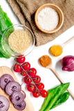 Composição caseiro dos ingredientes do paella com arroz, tomate, cebola na opinião superior do fundo branco da tabela imagens de stock royalty free