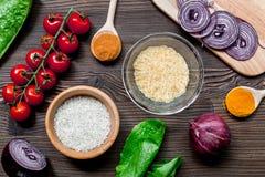 Composição caseiro dos ingredientes do paella com arroz, tomate, cebola na opinião superior do fundo de madeira da tabela fotografia de stock royalty free