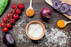 Composição caseiro dos ingredientes do paella com arroz, tomate, cebola na opinião superior do fundo de madeira da tabela imagem de stock