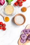 Composição caseiro dos ingredientes do paella com arroz, tomate, cebola no modelo branco da opinião superior do fundo da tabela fotos de stock royalty free