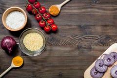 composição caseiro dos ingredientes do paella com arroz, tomate, cebola no modelo de madeira da opinião superior do fundo da tabe fotografia de stock