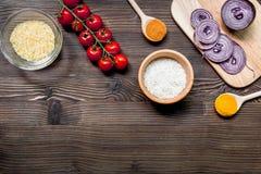composição caseiro dos ingredientes do paella com arroz, tomate, cebola no modelo de madeira da opinião superior do fundo da tabe fotografia de stock royalty free