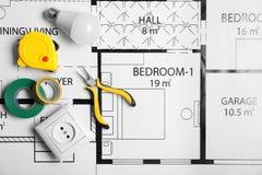 Composição colocada lisa com as ferramentas do eletricista no plano da casa imagens de stock royalty free