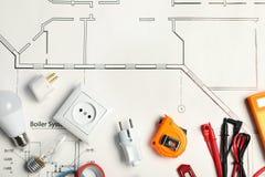 Composição colocada lisa com as ferramentas do eletricista no plano da casa foto de stock
