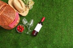 Composição colocada lisa com cesta, vinho e morangos do piquenique na grama fotos de stock