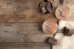 Composição colocada lisa com os frascos do leite de chocolate saboroso e do espaço para o texto no fundo de madeira imagem de stock