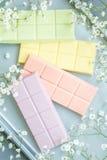 Composição com as barras de chocolate das cores pastel Foto de Stock