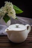 Composição com bule e flores na tabela de madeira Imagens de Stock Royalty Free