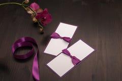 A composição com cartões feitos a mão e a orquídea florescem no colo roxo Imagens de Stock Royalty Free
