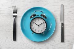 Composição com despertador, placa e utensílios no fundo claro foto de stock royalty free