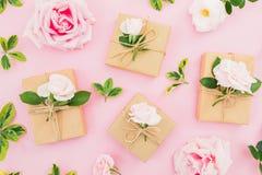 Composição com flores e caixas de presente das rosas no fundo cor-de-rosa Configuração lisa, vista superior Rosa vermelha foto de stock