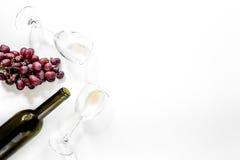 Composição com a garrafa do vinho tinto, dos copos de vinho e da uva vermelha na opinião superior do copyspace branco do fundo Fotos de Stock Royalty Free
