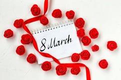 Composição com muitas rosas vermelhas, fita de seda do dia do ` s das mulheres, nota Imagem de Stock Royalty Free
